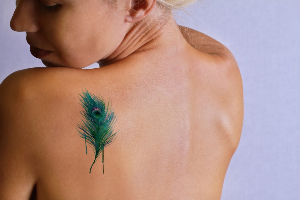 Beautiful young woman with tattoo on her back. Laser tattoo removal concept